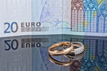 Gold and silver wedding rings on background of 20 Euro banknote