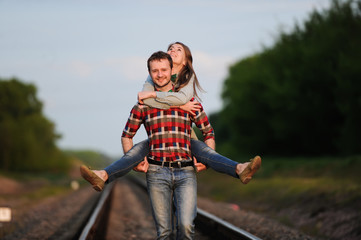 the guy and the girl walk along the railroad