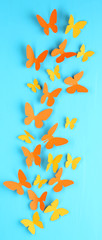 Paper butterflies on blue wooden board background