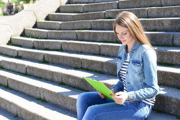 Happy student sitting on stairs in park