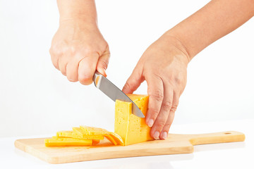 Female hands sliced cheese on a cutting board close up
