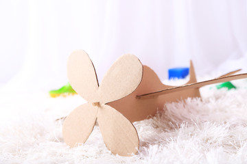 Paper airplane toy in room on the carpet