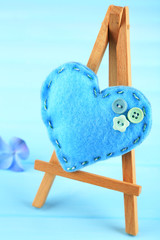 Beautiful heart  small decorative easel on blue background