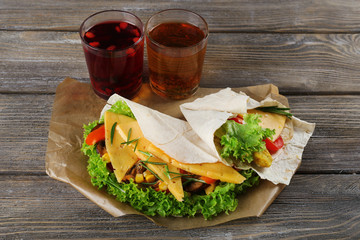 Veggie wrap filled with cheese and fresh vegetables on table