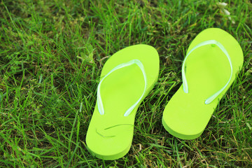 Bright flip-flops on green grass