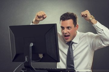 Excited businessman gesturing of joy with raised clenched fists