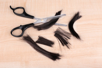 Cut hair and scissors on wooden background
