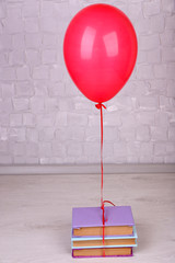 Color balloon with books on grey wall background