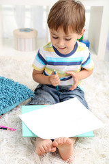 Cute little boy drawing in room