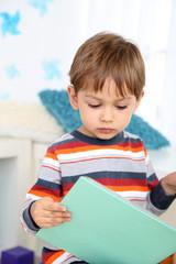 Cute little boy reading book in room
