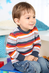 Cute little boy sitting on small chair in room