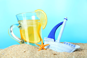 Cold tea in sand on blue background