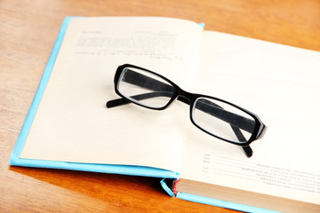 Composition with old book, eye glasses,  on wooden background