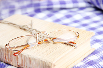 Composition with old book, eye glasses, and plaid