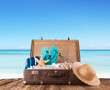 canvas print picture - Old suitcase with accessories on beach