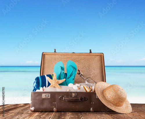canvas print picture Old suitcase with accessories on beach