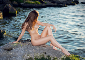 Nude girl posing in nature  near the river