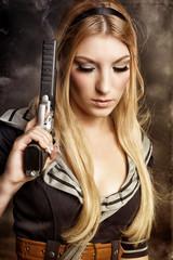 schöne blonde Frau mit rauchender Waffe