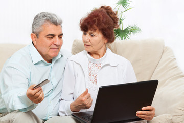 senior couple laptop credit card