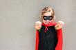 Superhero kid against blue sky background