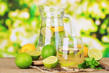 Fresh summer drink with lime and cloves in glass and jug,