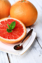 Half of grapefruit,  and spoon on plate on light background