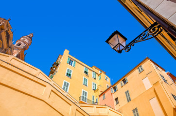 Yellow and orange buildings under blue sky in Menton.