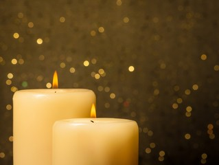 candles with flame on golden bokeh