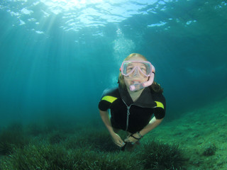 Young woman snorkeling dives in ocean