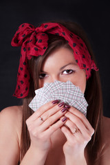 Pretty woman with playing cards in hands