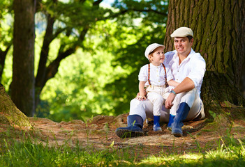 father and son sitting under an old tree