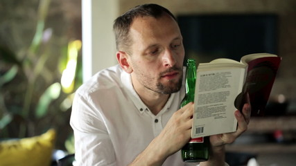Man reading book and drinking beer at home