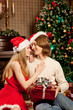 Nice love couple near the Christmas tree. Woman and man celebrat