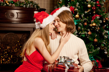 Nice young love couple near the Christmas tree. Woman and man ce