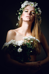Sexy woman with bouquet of daisies looking down