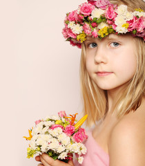 Beautiful little girl with flowers on light pink background