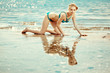 Beautiful slim woman on the beach by the sea. Luxury young girl