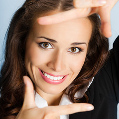 Businesswoman framing her face with hands, over blue