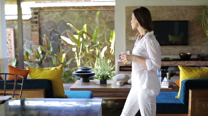 Beautiful woman drink juice and walking in luxury home