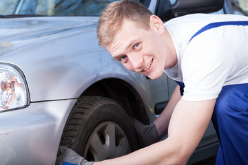 Auto mechanic checks a car tire