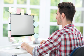 Man looking at a monitor with sticky note on it