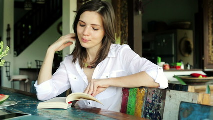Pretty woman reading book by the table at home