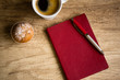 Red notebook with pen on wooden table