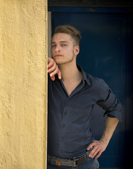 Attractive young blond man leaning against wall
