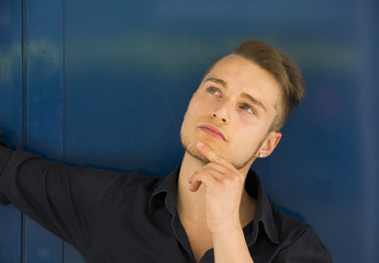 Attractive young man thinking, looking up with hand on his chin
