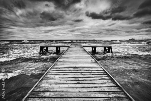 Fotobehang Golven Old wooden jetty during storm on the sea. Dramatic sky