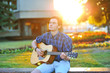 Young man playing on acoustic guitar in park