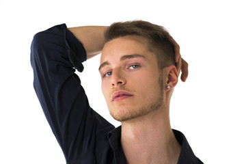 Cool confident blond young man with blue shirt, hand above head