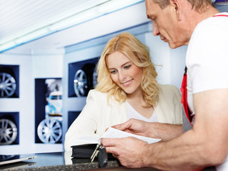 Female customer is satisfied with the service in a garage