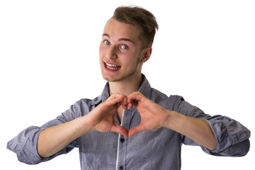 Happy blond young man doing heart or love sign with hands